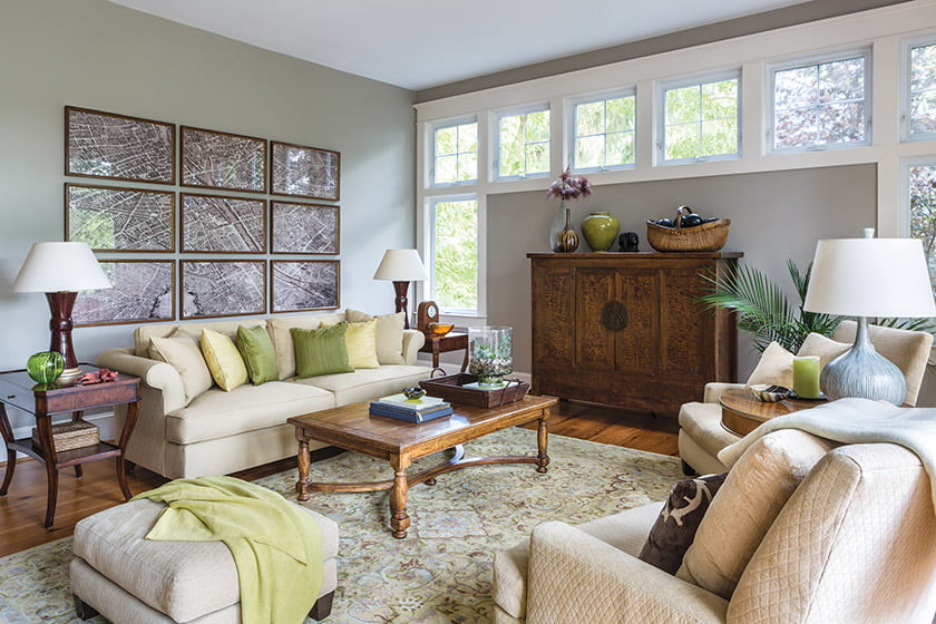 A parade of clerestory windows in the living room allows wall space for an antique Asian cabinet.