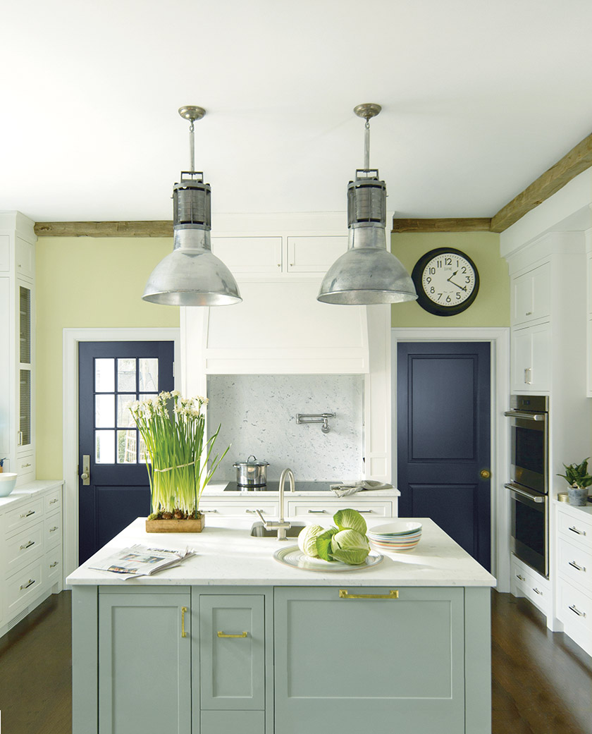 A deft mix of Benjamin Moore hues brings a classic kitchen to life. Walls painted fresh Fernwood Green complement a center island in soft Flora. Witching Hour adorns the doors for contrast.