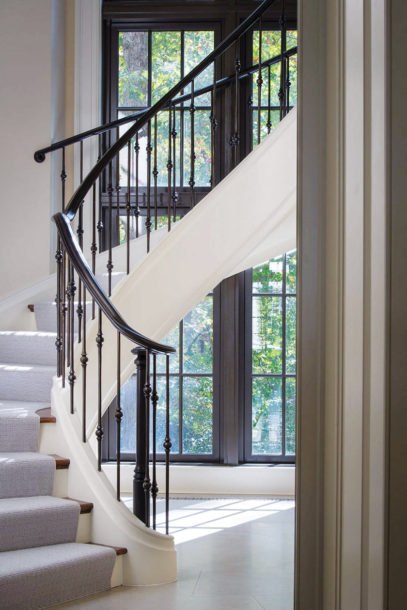 A curved, wrought-iron stair is a focal point at the end of a hallway.