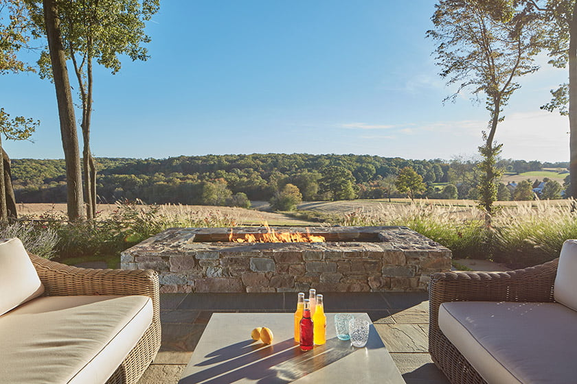 A stone fire pit on the terrace establishes a new vantage point from which to view the distant hills.