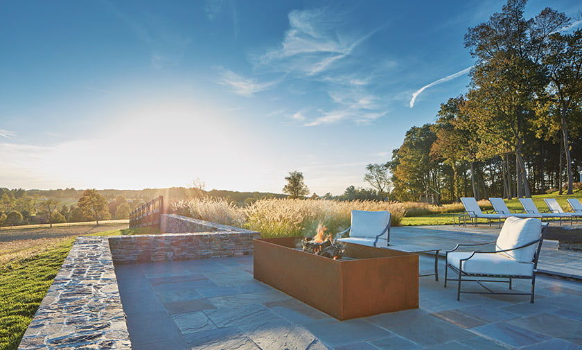 A steel fire pit set in a step-down alcove off the bluestone pool deck overlooks farmland to the south.