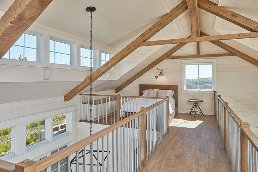 Beams salvaged from an old barn on site found a second life as rafters; a loft for afternoon naps is accessible by ladder.