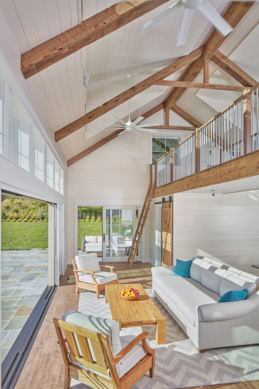 The owners furnished the pool house with relaxed wooden pieces and neutral upholstery.