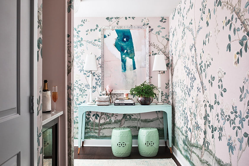 Schumacher wallpaper, an abstract work from Zoe Bios Creative and garden stools set the scene in the entry hall.