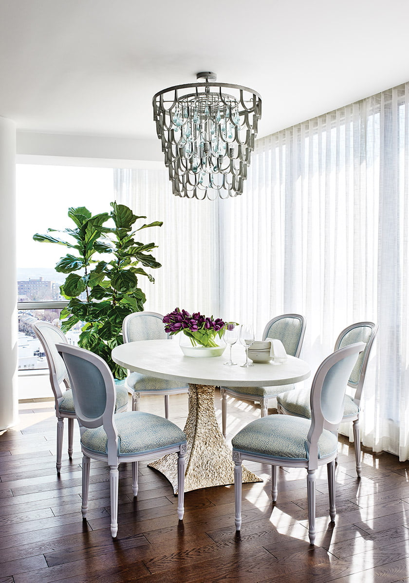 A glamorous table and chandelier by Made Goods mingle with Highland House chairs in the dining area.