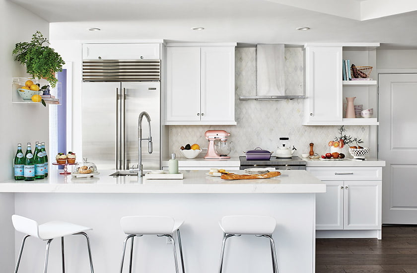 The crisp, white kitchen features quartz countertops, cabinets from Cornerstone Kitchen & Bath and a Rohl faucet.