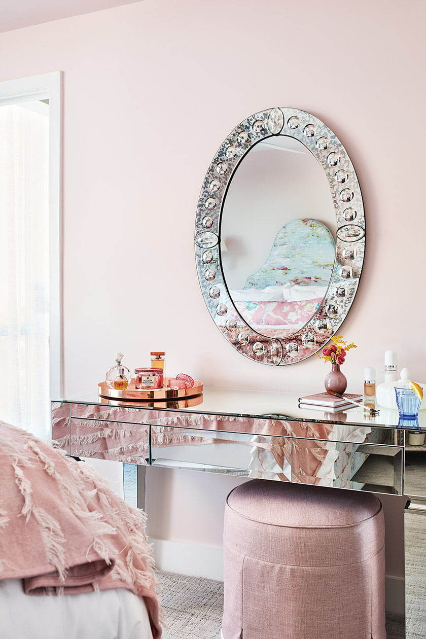 A Worlds Away desk-turned-vanity and a Made Goods mirror grace the master bedroom.