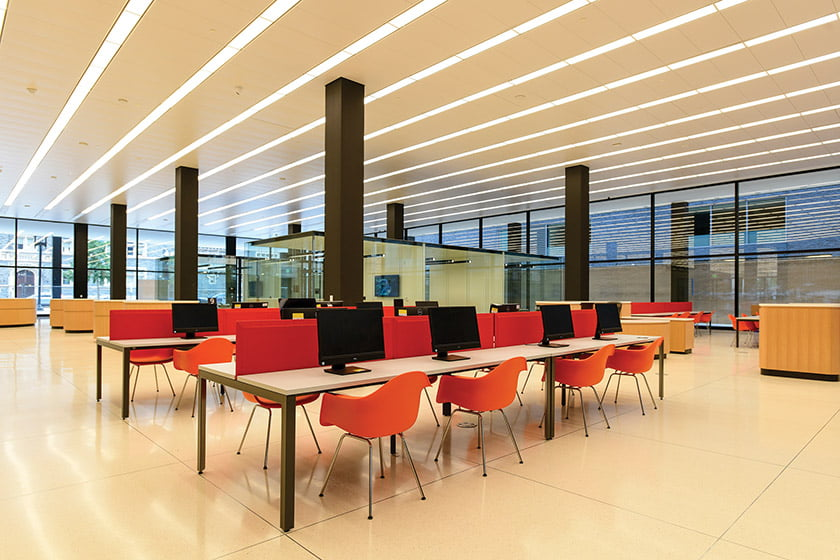 In the Digital Commons, computers and glass-enclosed meeting rooms provide welcoming community workspaces.
