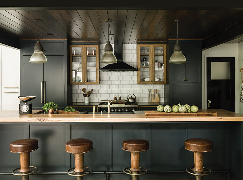 The kitchen cabinets, crafted by Danish Builders, mix natural white oak and a blue-black painted finish.