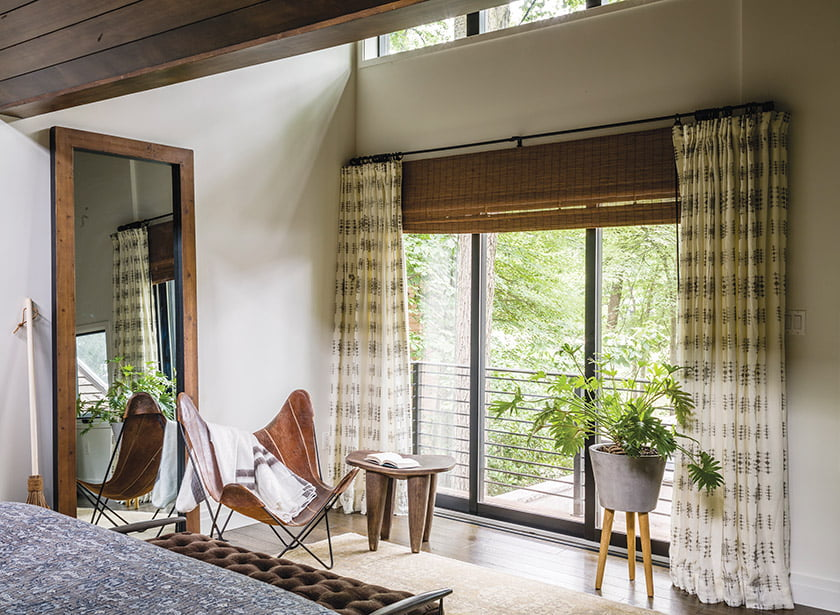 An antique Mamluk rug mingles with a 1960s Butterfly chair. Window sheers in Raoul Textiles fabric frame the view.