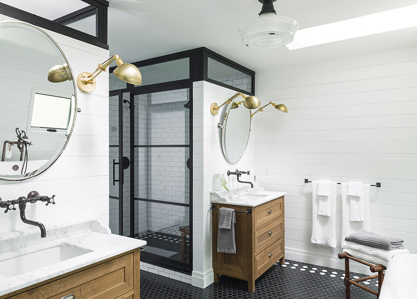 Liess found the wall-mounted library lights on Etsy. Honed marble tops the white-oak vanities.