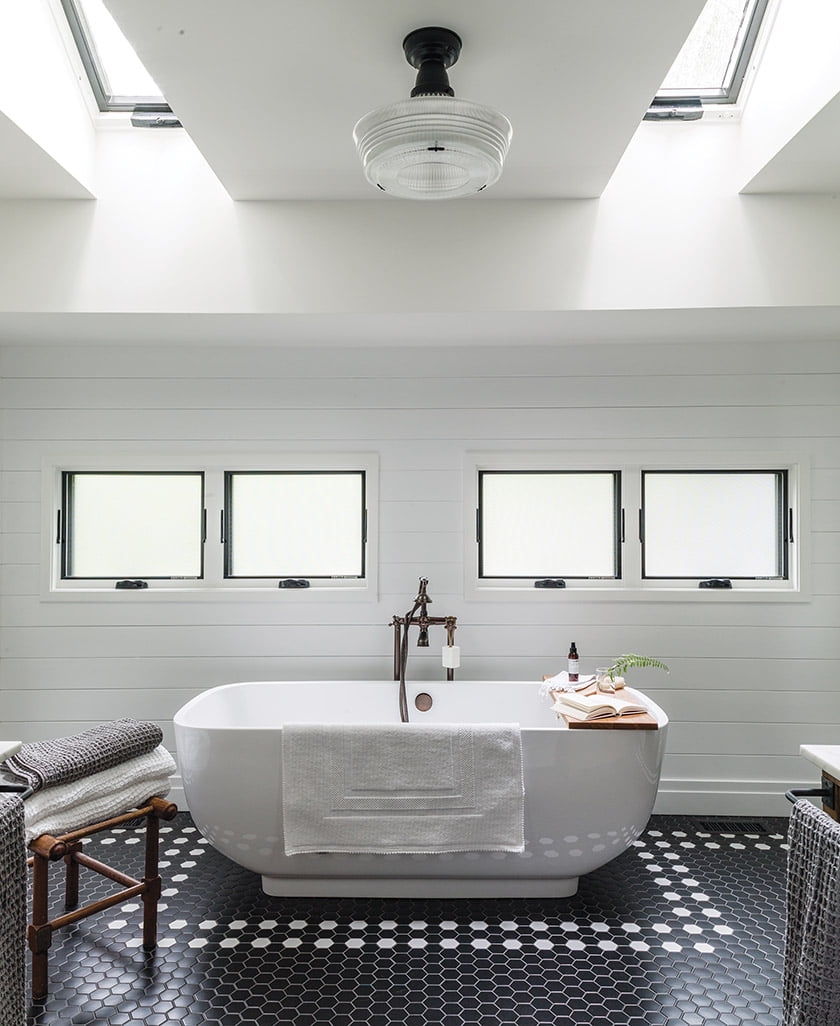 A Signature Hardware soaking tub serves as the centerpiece while a steel-framed shower ups the industrial vibe.