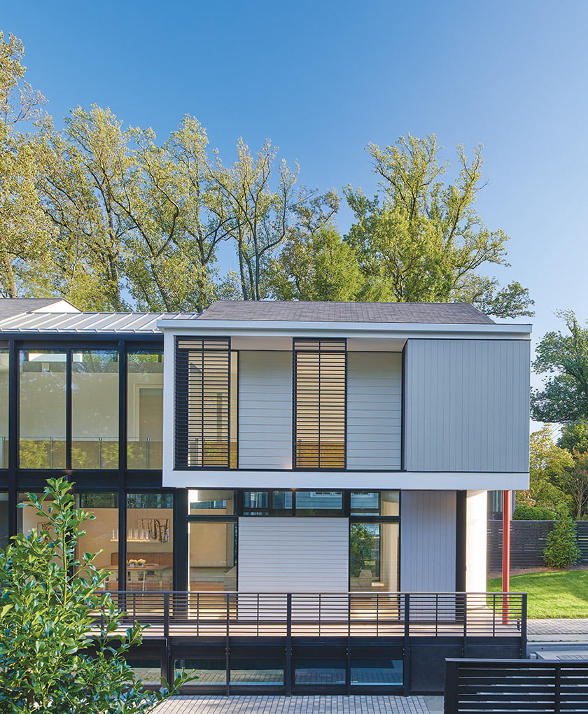 The street-facing side of the house is punctuated by louvers and railings that act as layers for privacy.