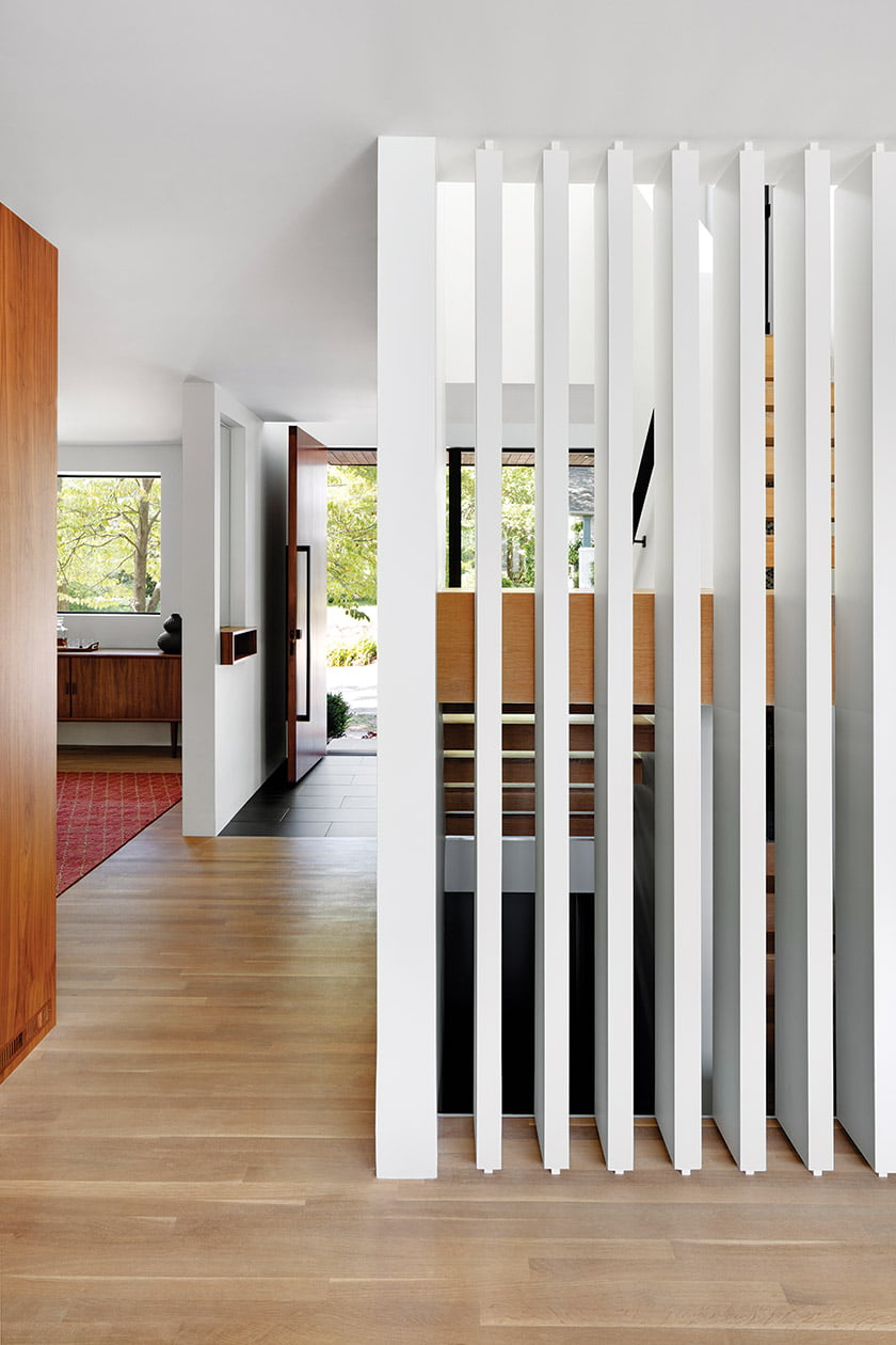 The open stair is screened on one side by slats for privacy.