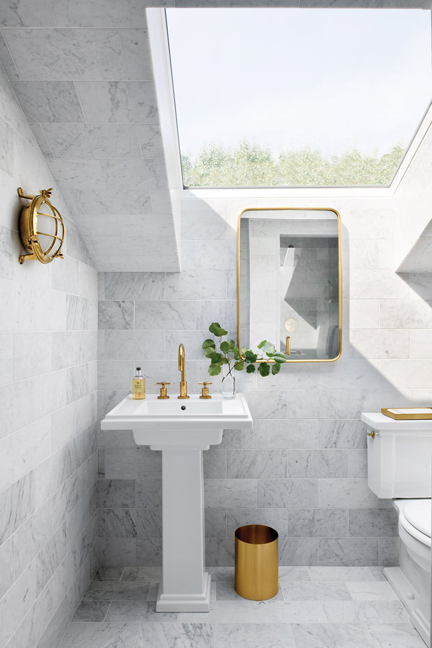 Carrara marble and brass accents embellish a jewel-box guest bathroom bathed in natural light via a glass ceiling panel.
