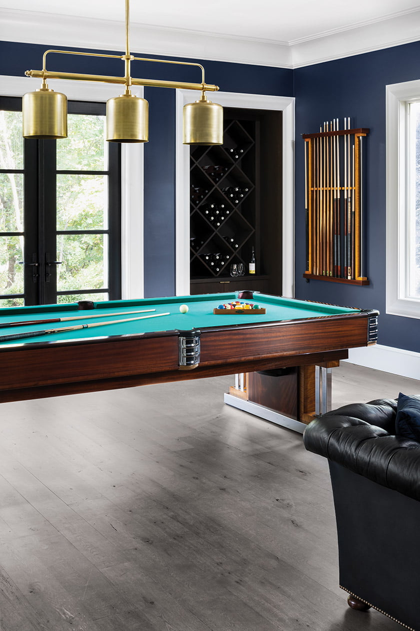 In the clubby guest house, an Olampia light fixture hangs above a pool table restored Billiards by Brandt.