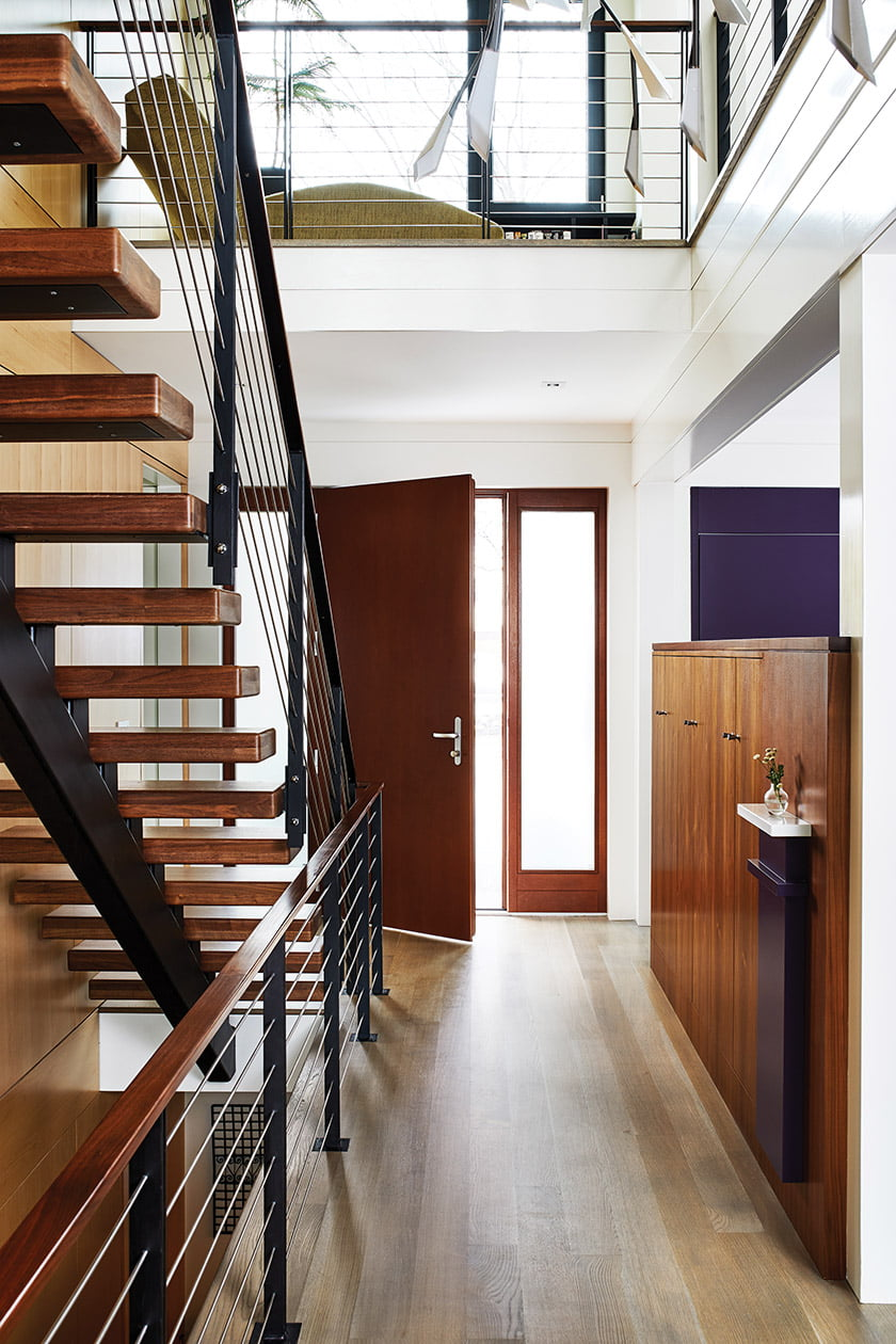 The light-filled entry and staircase are flanked on one side by maple panels.