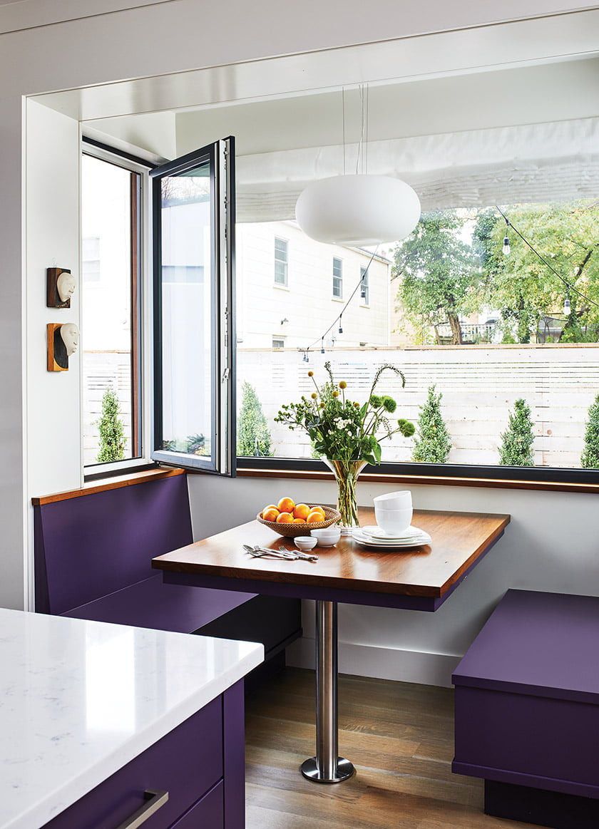 Built-in seating in the breakfast nook combines with a walnut-topped table and a Eurofase pendant.