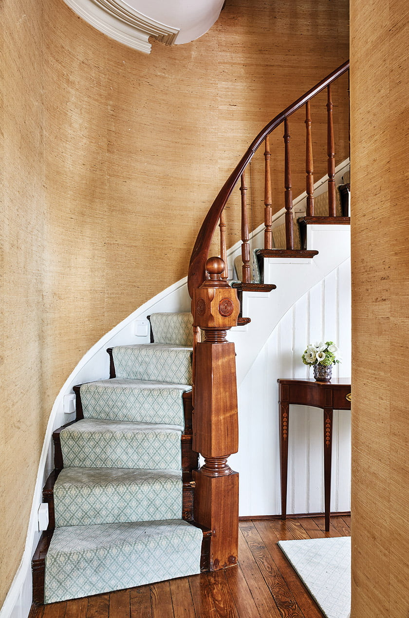Gold grass-cloth wall covering on the curved stair inspired the dining room's look.