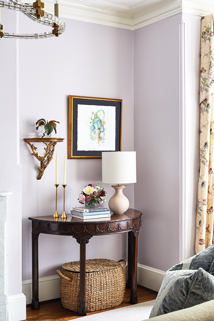 An antique demi-lune table is one of two flanking the fireplace.