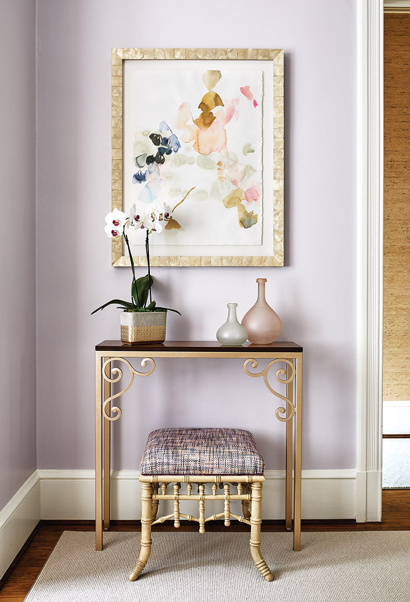 A console finished in metallic gold is paired with a mixed-media piece by Elise Morris.
