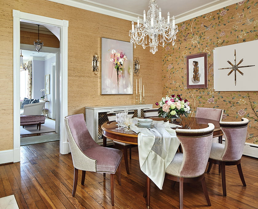 The dining room grass cloth is embellished on one wall with a tree-of-life motif. The sideboard is by Century.