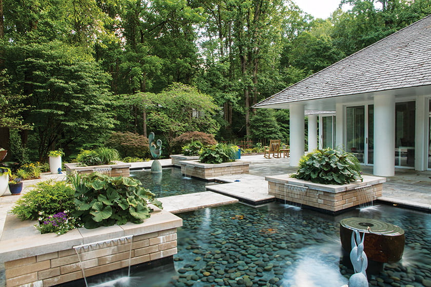 Large, square planters anchor this project, which boasts waterfalls and pools lined with Mexican beach pebbles.