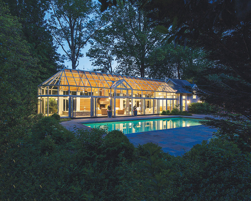 A gabled glass frame ushers guests into the structure; folding NanaWalls open to the pool.