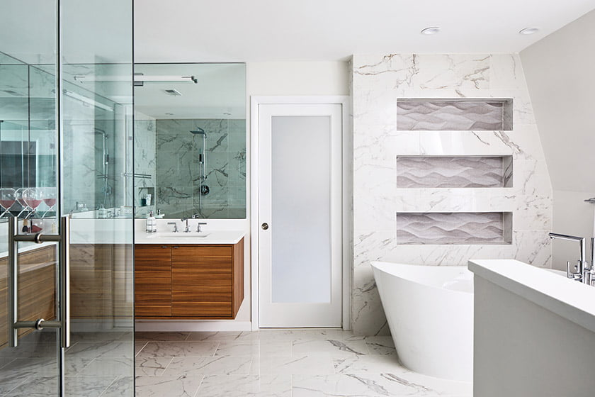 Wall niches embellished with 3D porcelain-tile panels and integrated LED lighting create a focal point.