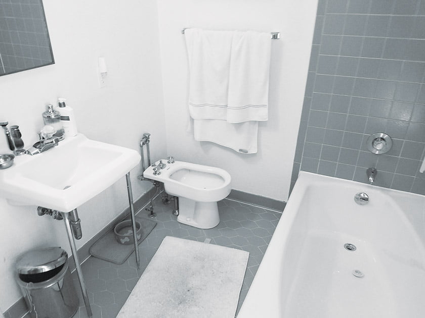 Before: The bath was dated and dysfunctional, with drab ceramic tile on the walls and floor.