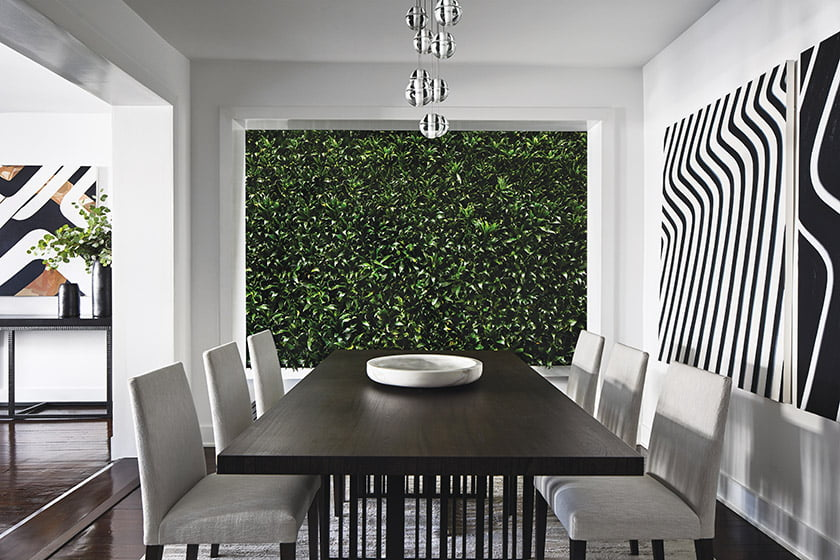 A living wall is a focal point in the dining room, which combines a Molteni table and Holly Hunt chairs.