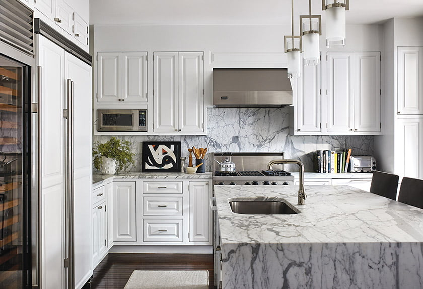 A waterfall countertop of statuary marble takes center stage in the kitchen.