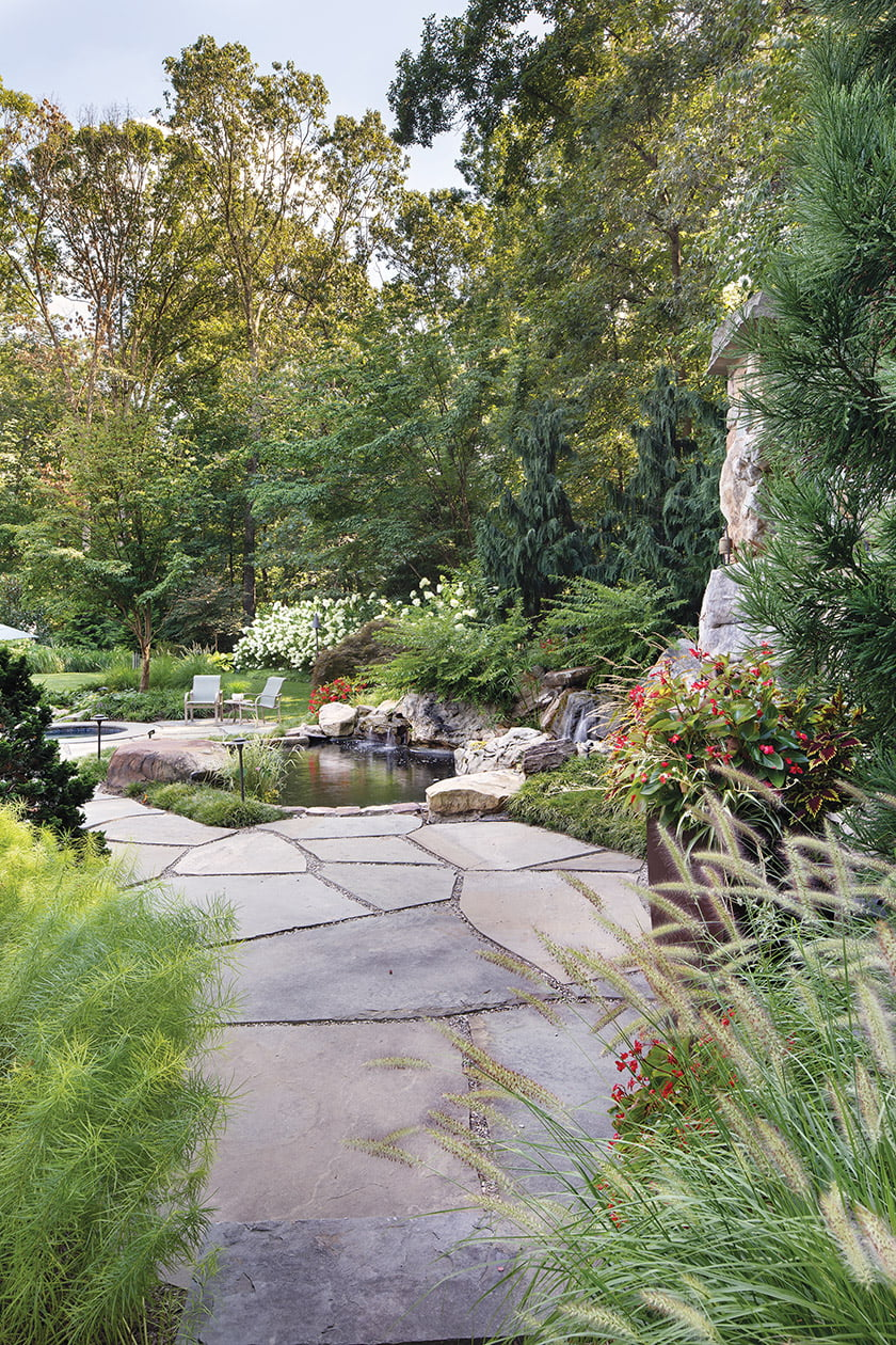 Irregular flagstone conveys a casual, rustic feel around the koi pond, a favorite element of the owners' landscape.