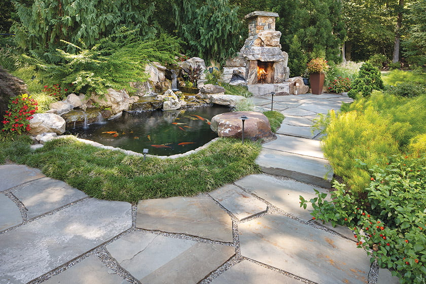 The fireplace occupies a corner spot for gathering beyond the koi pond framed in Mondo grass.