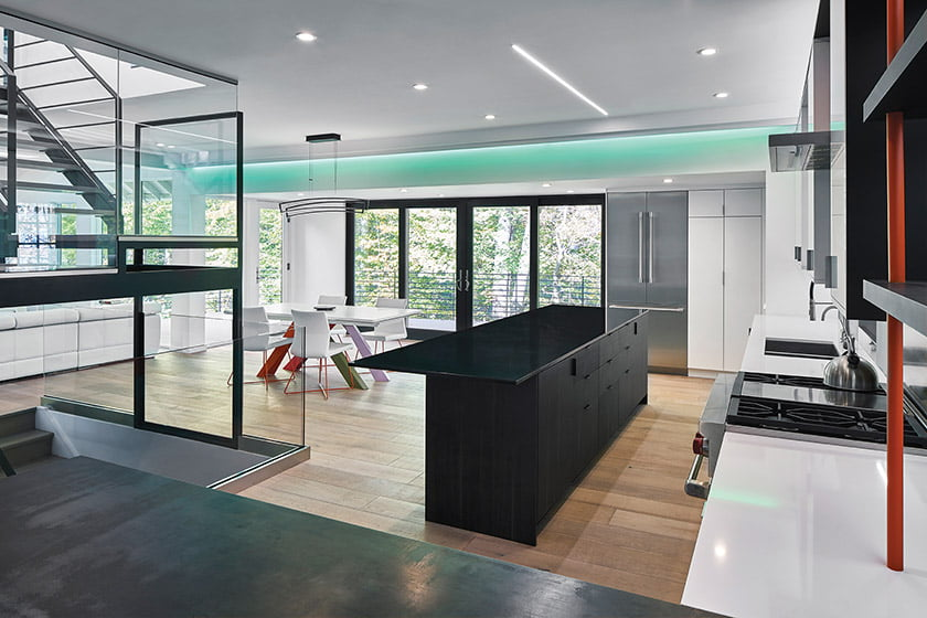 The open-plan main floor, featuring color-changing LED lights, spills out to the deck through sets of glass doors.