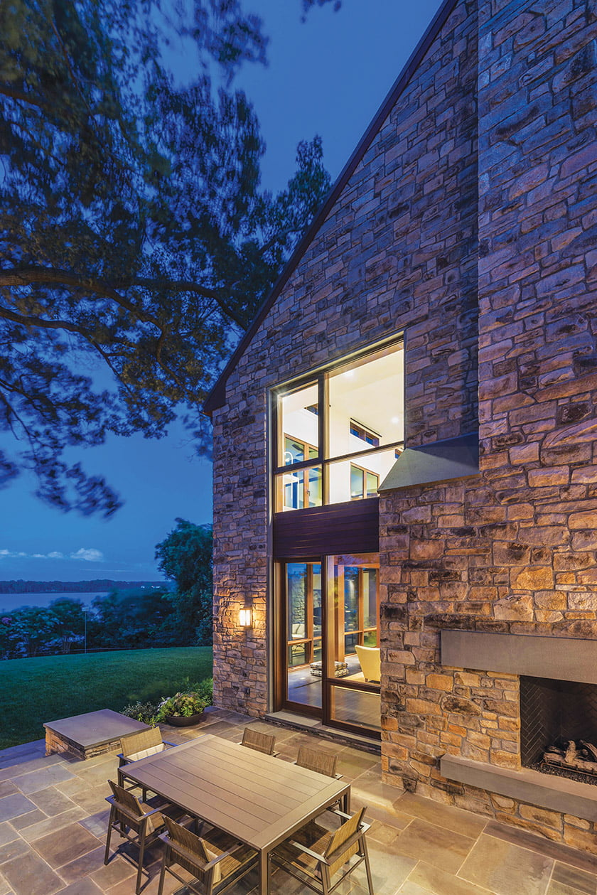 A dining patio boasts an outdoor fireplace built into the side of the house.