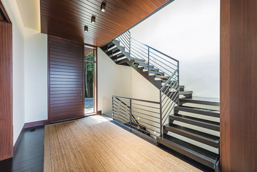 An industrial-style, steel-and-wood staircase in the front hall complements mahogany ceiling panels and a matching front door.