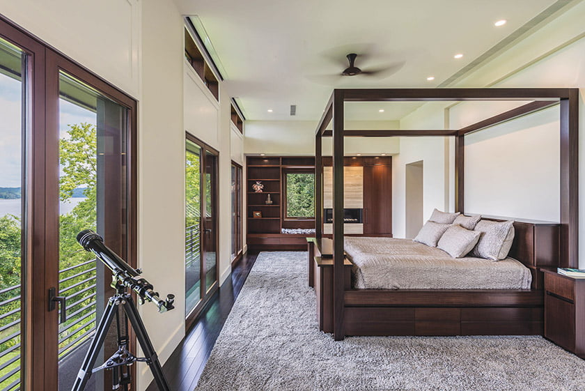 The master suite features a custom mahogany bedstead, built-ins framing a fireplace and mahogany-framed doors opening out to a balcony.