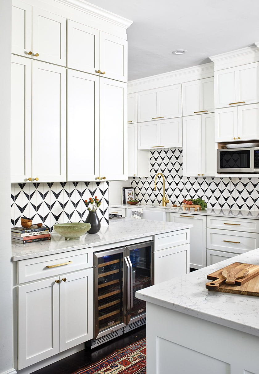 A wine fridge is conveniently located by the island for easy entertaining. White, ceiling-height cabinets create abundant storage and highlight the statement-making backsplash tile; part of Ann Sacks' Benton Mosaics collection, it combines White Thassos and Nero Marquina marble.