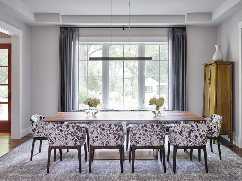 A walnut table and low-backed, velvet-covered chairs from Modway anchor the dining room.