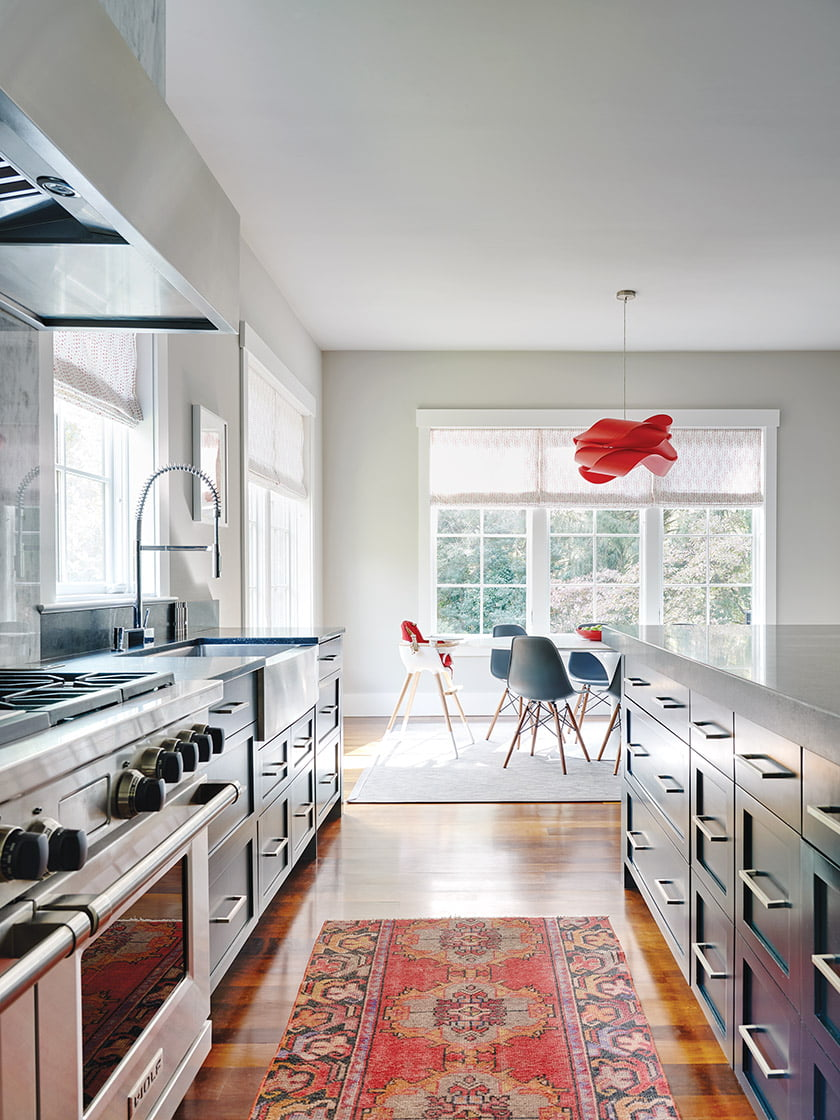 In the kitchen, a Saarinen Tulip Table and Eames chairs were sourced at Design Within Reach.