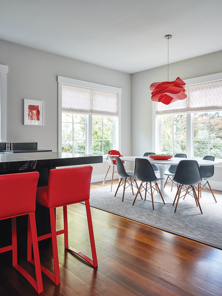The red walls in the kids' playroom pick up the bright hue of the stools and light fixture in the kitchen.