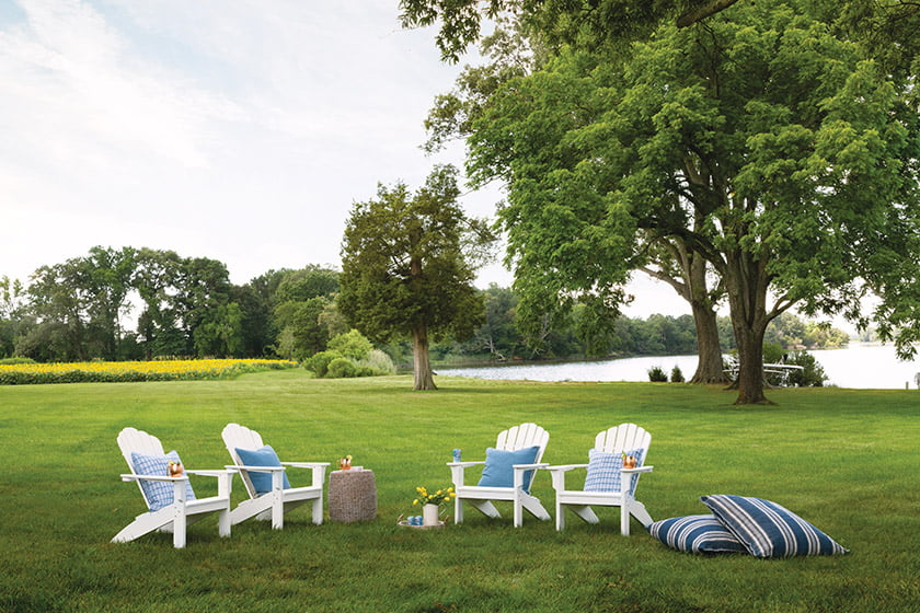 The house overlooks picturesque Hunting Creek, with a lawn bordered by a field of sunflowers.