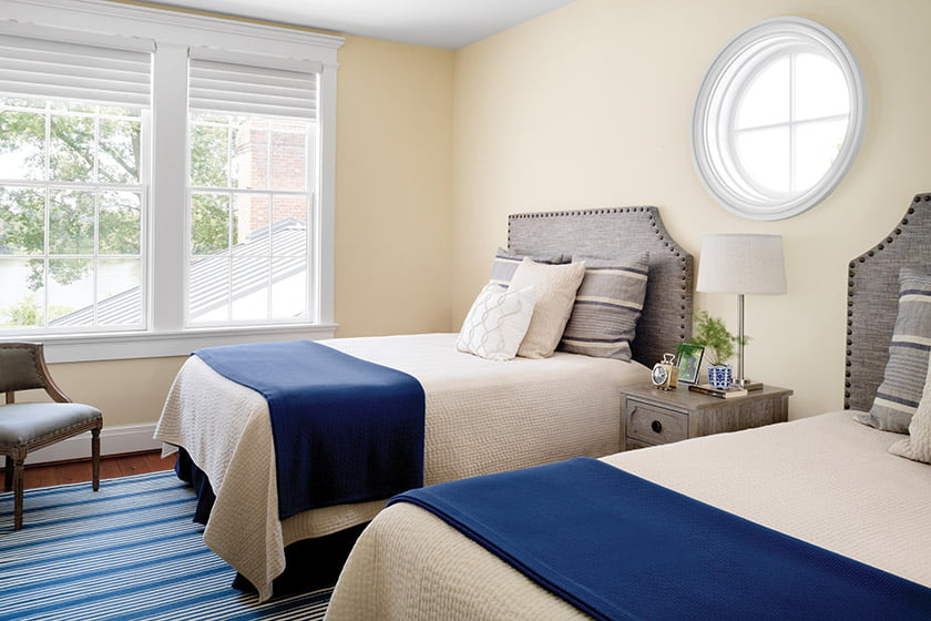 In one guest room, headboards were customized to accommodate the porthole window.