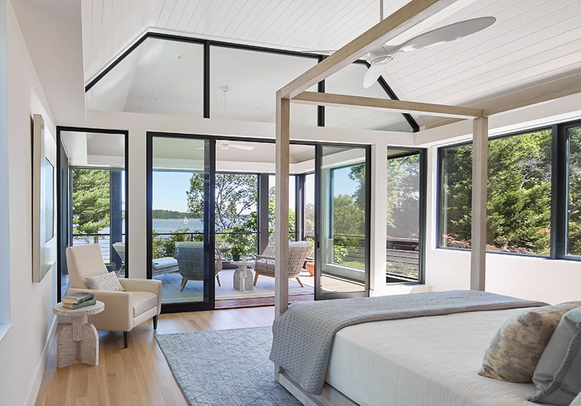 The owner's bedroom opens to a screened porch beneath a raised, wood-paneled ceiling.