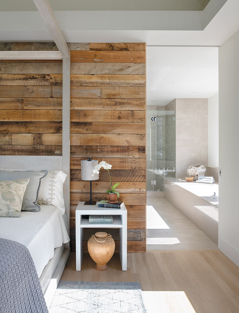 Reclaimed-oak barn wood in the owner's suite contrasts with Crema Marfil marble in the bath.