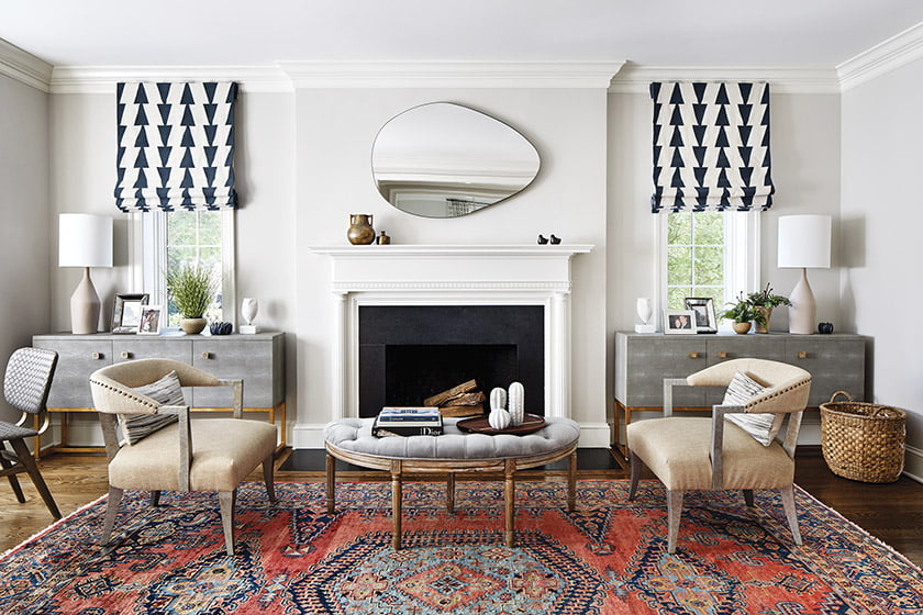 Sideboards flank the fireplace, their symmetry offset by an asymmetrical mirror.