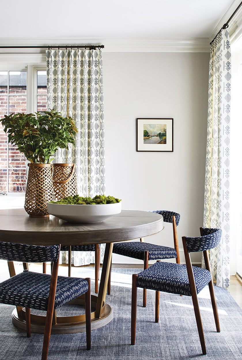 In the dining room, a Mitchell Gold + Bob Williams table keeps company with vintage chairs upholstered in Pindler fabric.