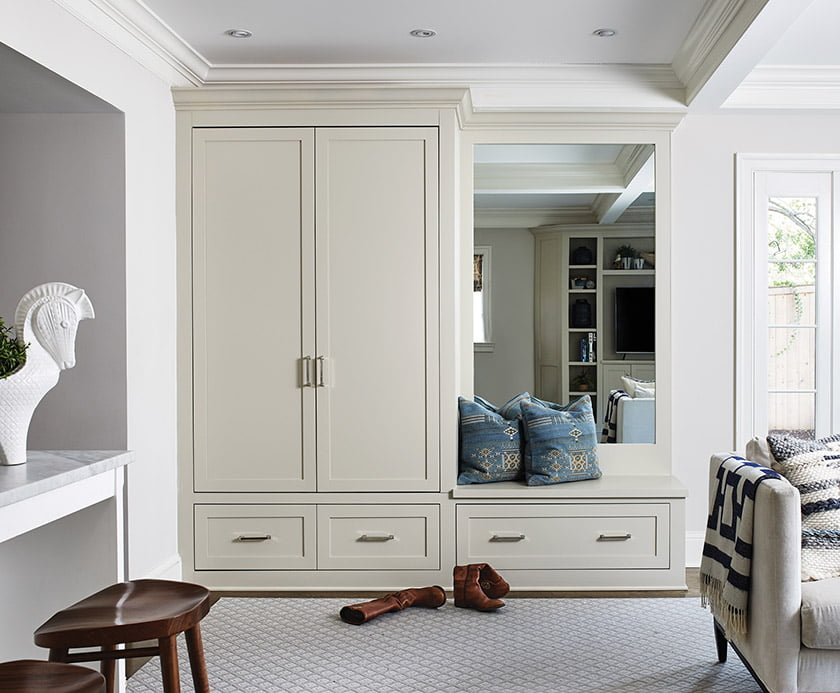 In  a corner of the  family room, Ireland installed built-ins to house the television and serve as a mudroom area.