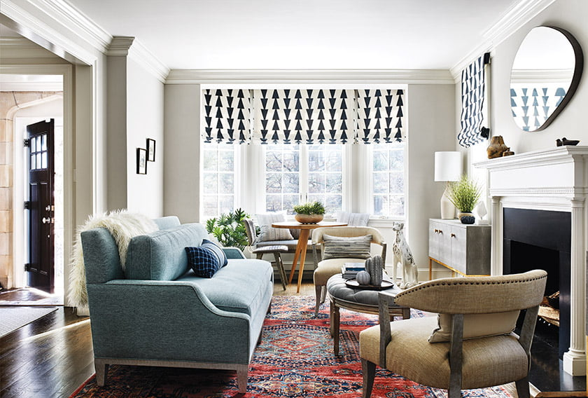 In the living room, a vintage rug grounds a custom sofa and chairs, all upholstered in Osborne & Little fabric.